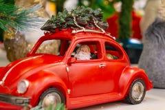 Santa Claus i en röd bil bär en julgran på taket av bilen arkivbild
