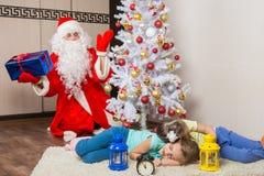 Santa Claus i helgdagsafton för nya år förvånades som ser de sova barnen för träd två royaltyfria bilder