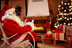 Free Santa Claus In Room Near Fireplace Read Whishing List For Christ Royalty Free Stock Photo - 82320135