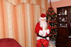 Santa Claus and Christmass tree during Xmas with happy girl Royalty Free Stock Images