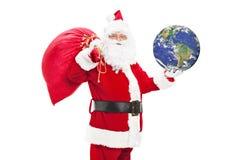 Santa Claus innehavpåse av gåvor och jorden Arkivbilder