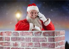Santa claus inside a chimney talking on mobile phone Royalty Free Stock Photography
