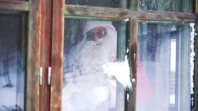 Santa Claus inside the house at window.