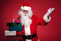 Santa claus is inviting you to get some presents. On red studio background Stock Photo