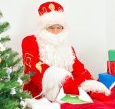 Santa Claus ironing clothes. Royalty Free Stock Images