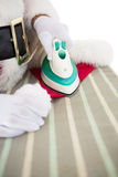 Santa claus ironing his hat Royalty Free Stock Photography