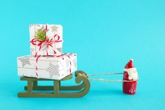 Free Santa Claus Is Carrying Wooden Sleigh With Two Gift Boxes Wrapped Of White-gray Paper, Decorated Of Fir Branch On Blue Background Stock Image - 132665421