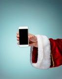 Santa Claus jugeant le smartphone mobile prêt pour le temps de Noël Image stock