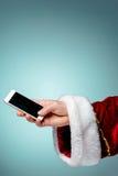 Santa Claus jugeant le smartphone mobile prêt pour le temps de Noël Photos stock