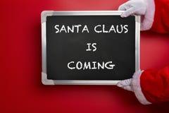 Santa Claus jugeant un panneau de craie noir écrit avec SANTA CLAUS VIENT sur le rouge Photographie stock libre de droits
