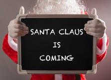 Santa Claus jugeant un panneau de craie noir écrit SANTA CLAUS VIENT Image libre de droits