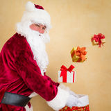 Santa Claus juggling Christmas gift boxes Royalty Free Stock Photo