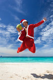 Santa Claus jumps with coconut on beach Stock Image