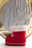 Santa Claus känga med det enorma ett euromyntet i bakgrunden Royaltyfria Bilder
