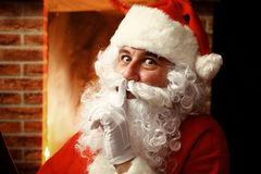 Santa Claus keeping forefinger by his mouth Stock Images