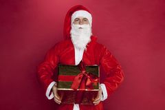 Santa Claus keeps a beautifully wrapped gift. On the red background Royalty Free Stock Photography