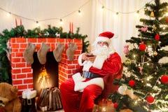Santa Claus in Kerstmis drinkt thee, koffie van een mok in een cha stock foto's