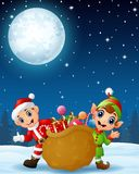 Santa claus kid with cartoon elf and a sack full of gifts in the winter night background Royalty Free Stock Images