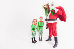 Santa Claus and Kids dressed in Elven costumes. North Pole. Stock Photo