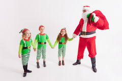 Santa Claus and Kids dressed in Elven costumes. North Pole. Wish .  Claus and Little Kids dressed in Elven costumes. North Pole. Elf friend. Cristmas Scene at Stock Images