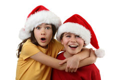 Santa Claus kids isolated on white. Kids wearing Santa Claus hats pointing isolated on white Royalty Free Stock Images