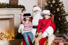 Santa claus and kids in vr headsets. Kids in vr headsets sitting on santa claus knees at home Stock Photo
