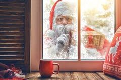 Santa Claus klopft am Fenster Lizenzfreies Stockbild