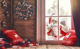 Santa Claus is knocking at window. Merry Christmas! Santa Claus is knocking at window. Room decorated for holidays. View indoors home royalty free stock image