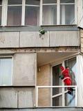 Santa Claus kommer ner repet på balkongen av en byggnad Har dig beställde redan feriegåvor för ditt hushåll? royaltyfri foto
