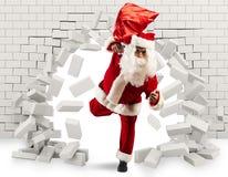 Santa Claus kommt herein, um das Geschenk zu liefern, indem sie ein Loch in der Wand macht lizenzfreie stockfotografie