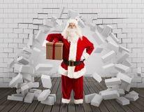 Santa Claus kommt herein, um das Geschenk zu liefern, indem sie ein Loch in der Wand macht lizenzfreie stockbilder