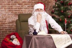 Santa Claus kontrollerar hans lista Royaltyfri Bild