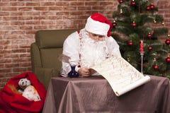 Santa Claus kontrollerar hans lista Royaltyfria Foton