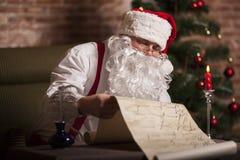Santa Claus kontrollerar hans lista Royaltyfri Foto