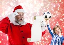 Santa Claus läs- önskelista och upphetsad pojke med fotboll Royaltyfri Fotografi
