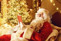 Santa Claus läser en bok i ett rum med en spis i Chri royaltyfria bilder