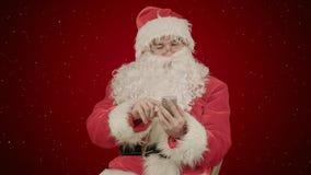 Santa Claus läser och överför textmeddelanden från hans mobiltelefon på röd bakgrund med snö Royaltyfri Foto