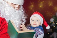 Santa Claus läsning för behandla som ett barn boken med julsaga Arkivfoto