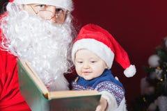 Santa Claus läsning för behandla som ett barn boken med julsaga Arkivbild
