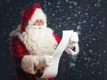 Santa Claus läsning från en lång lista Arkivbild