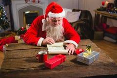 Santa Claus läsningsnirkel i vardagsrum Arkivfoto