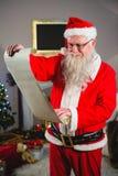 Santa Claus läsningsnirkel i vardagsrum Arkivbild