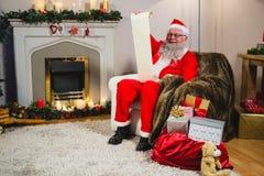 Santa Claus läsningsnirkel i vardagsrum Arkivfoton