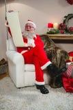 Santa Claus läsningsnirkel i vardagsrum Royaltyfria Foton