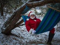 Santa Claus-Lügen entspannten sich in der Hängematte im Winterwald Lizenzfreies Stockbild