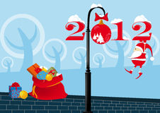 Santa Claus on a lamppost. Santa Claus is hanging on a lamppost in figures c 2012 Stock Photos
