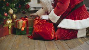 Santa Claus laying out presents under christmas tree stock video footage