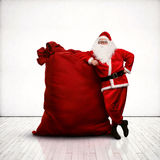 Santa Claus leaning on huge red sack Stock Photo