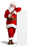 Santa Claus leaning a white board mock up advertisement on a white background. Royalty Free Stock Photo