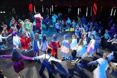 Santa Claus leder barnen som en gladlynt ferie dansar bär den santa för natten för illustrationen för julclaus gåvor vektorn Sant Royaltyfria Bilder
